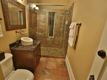 bathroom with shower, vanity basin, white towels