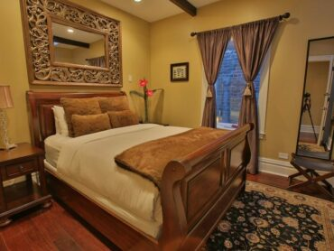 Euro bedroom with sleigh bed, beautiful mirror and luxurious linens