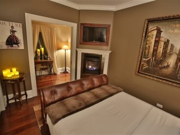 bedroom with corner fireplace, candles, painting on wall