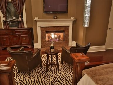 bedroom with blazing fireplace, 2 chairs with table in between