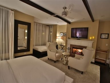 bedroom with white furnishings, blazing fireplace, tv above