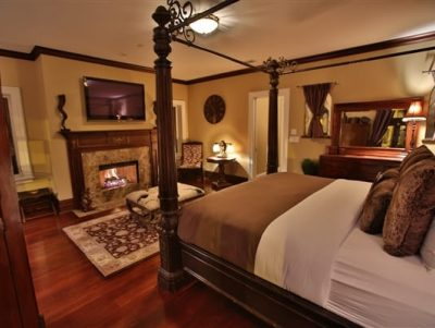 bedroom with 4-poster bed, blazing fireplace, tv above