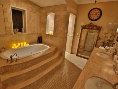jacuzzi tub with steps leading up, 2 vanity sinks, large mirror