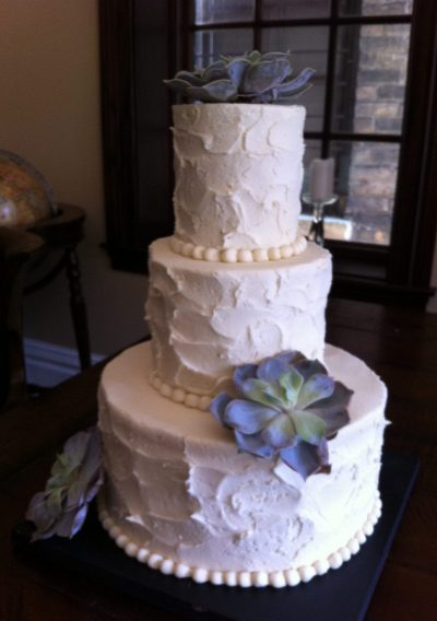Wedding cake with white frosting and a decadent flower