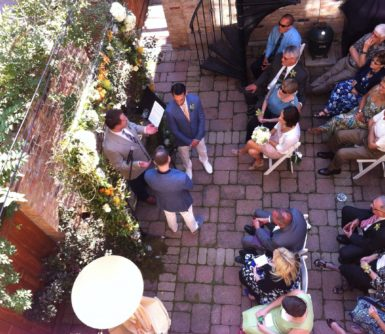 A wedding taking place in the courtyard with a beautiful arrangement of flowers
