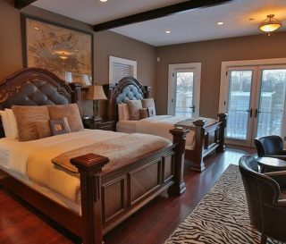 Two large beds and dark hardwood floors in the Florencia Suite
