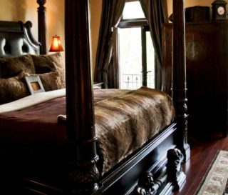 Large 4-poster bed of dark wood with luxurious furnishings