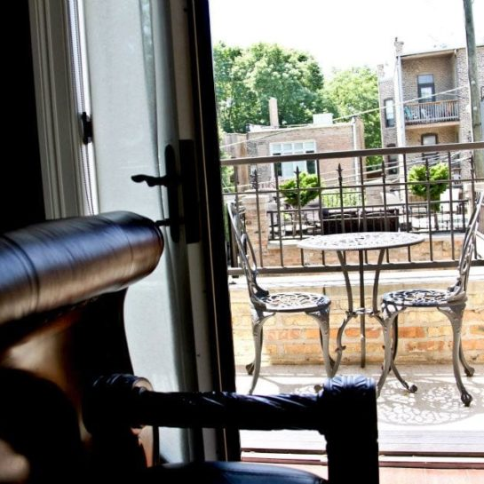 looking out onto deck with two wrought iron chairs and table