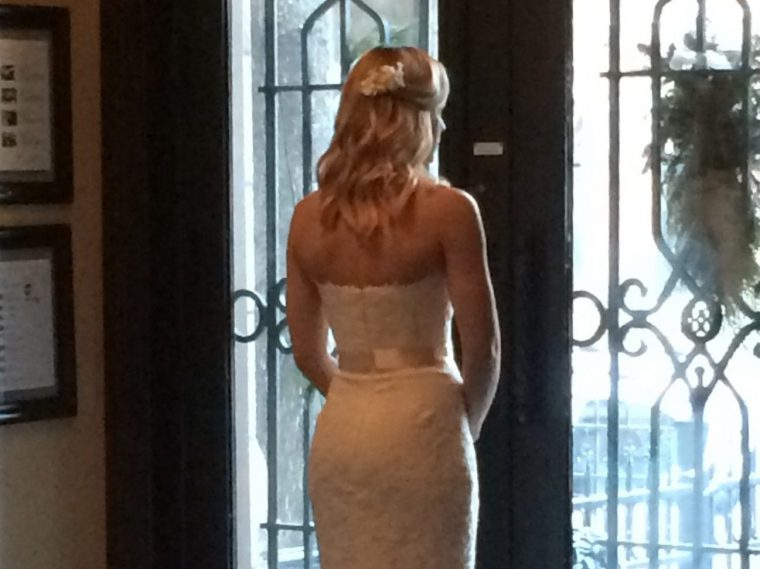 bride standing in doorway in front of glass doors