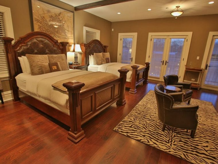 Florencia Suite with 2 beds and chairs and dark wood floor