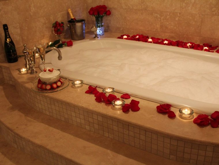 jacuzzi tub filled with bubbles, rose petals and candles