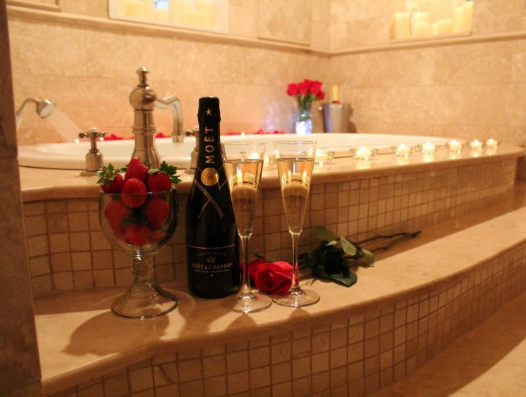 glass of strawberries and bottle of champagne with 2 champagne flutes and red rose on side of jacuzzi tub